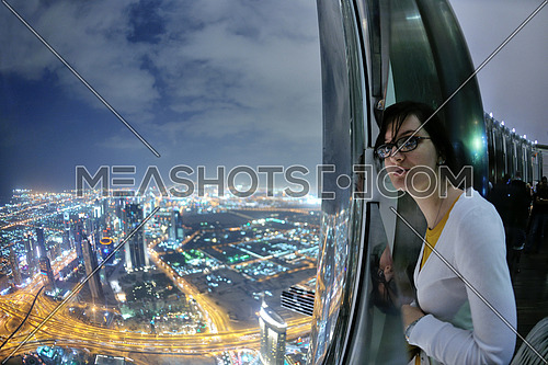 beautiful woman relax on balcony with  amazing night city view in background