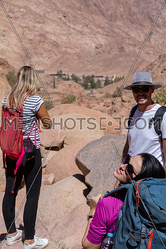 Long shot for a group of tourists wearing backpacks standing and talking while exploring Sinai Mountain for wadi Freij at day.