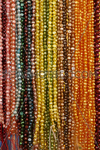 Close up many strings of colorful bead necklaces on retail display, low angle view