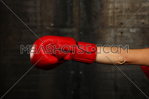Woman hand in red boxing glove punching over dark background, close up, profile side view