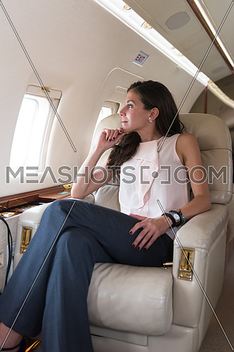 Portrait of a young middle eastern successful businesswoman sitting on a private jet with a tablet in hands