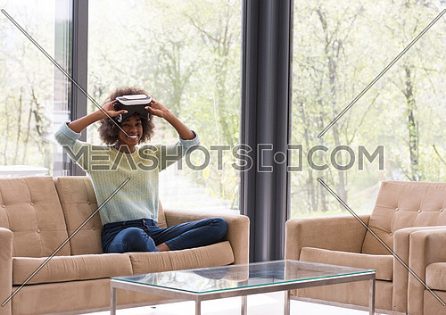 Happy african american girl getting experience using VR headset glasses of virtual reality at home
