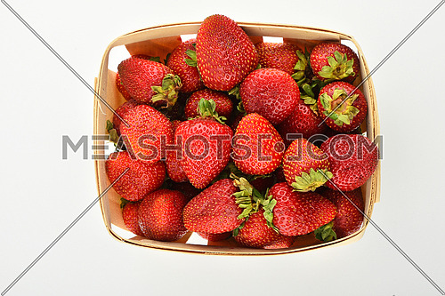 Mellow fresh summer strawberries in wooden basket isolated on white background, top view