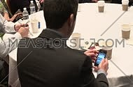 close shot from behind for a business man wearing suit and using his Smart phone in a conference.