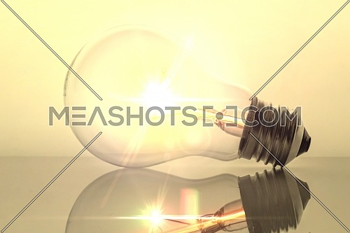 Old bulb filament isolated backlit on white background, conceptual image