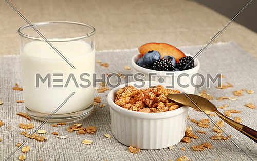 Close up portion of muesli granola breakfast with fruits and berries, with glass of milk, high angle view