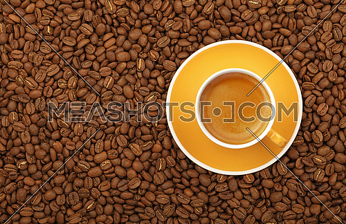 Full espresso in yellow cup with saucer on background of roasted coffee beans, elevated top view, close up