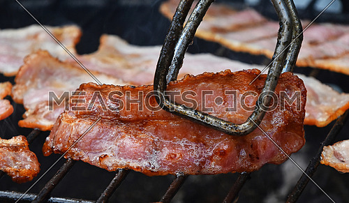 Tongs holding crispy smoked grilled barbecue bacon slice, cooked on bbq smoke grill, close up