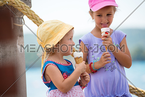 adorable little girls eating ice cream on beach by the sea during Summer vacation