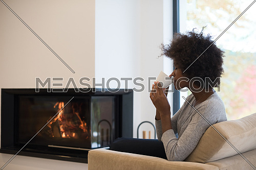 Happy joyful african american woman drinking cup of coffee relaxing at fireplace. Young black girl with hot beverage heating warming up. autumn at home.