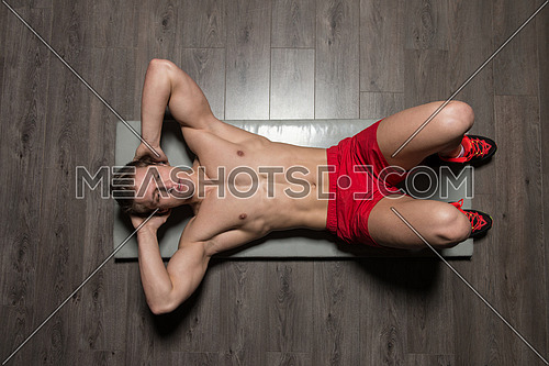 Young Healthy Man Exercising Abdominals On Foor