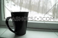View of a black coffee cup in a window ledge as a winter snow storm blows outside.