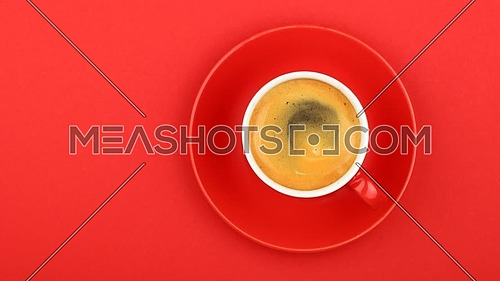 Close up one full cup of espresso coffee and saucer over vivid red paper background with slow motion animated cinemagraph spin of coffee froth