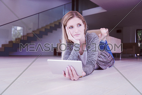 beautiful young women used tablet computer on the floor of her luxury home