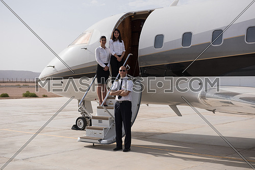 portrait of a successful middle eastern pilot with young beautiful stewardess at the airport in front of the private airplane