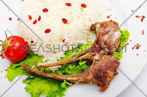 Lamb ribs with rice served in the plate