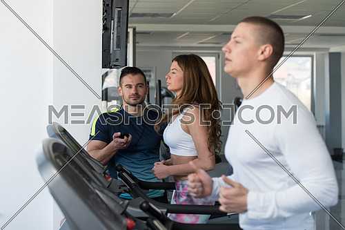Group Of Young People Running On Treadmills In Gym Or Fitness Club While Personal Trainer Measure Time On Stopwatch