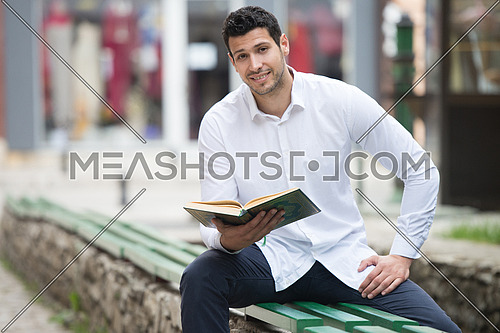 Humble Muslim Man Is Reading The Koran Outdoors