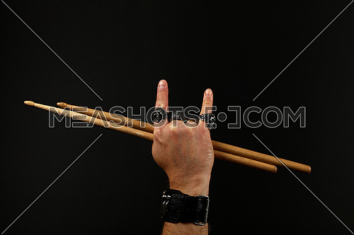 Close up man hand with devil horns rock gesture sign, metal rings and bracelet holding two drumsticks over black background, side view