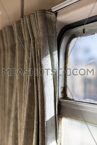 Touristic train in Egypt from Cairo to Aswan. A fuzzy window and curtains are open. Close up