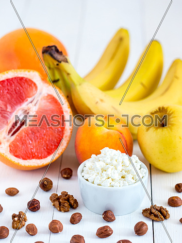 Healthy breakfast: cottage cheese, fruits and nuts on white wooden background. Dieting, healthy lifestyle concept meal. Vertical