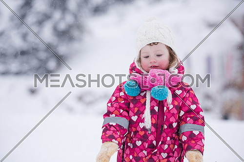 portrait of happy smiling little girl outdoors, having fun and playing on fresh snow on snowy  winter day