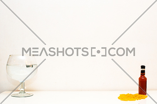 Pasta, Hot sauce and a floating candle on White Background and white table