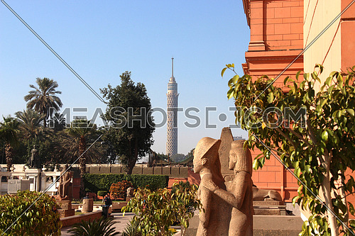a photo from the yard of the Egyptian Museum showing the garden, statues & Cairo tower