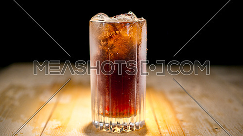 Glass of Cold Fizzy Drink on a wodden table