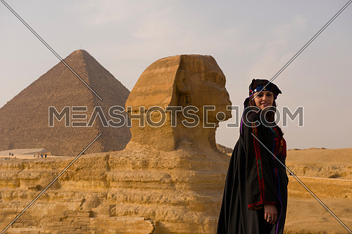 egyptian woman in traditional clothes in front of ancient grea giza pyramids  and sphinx profile