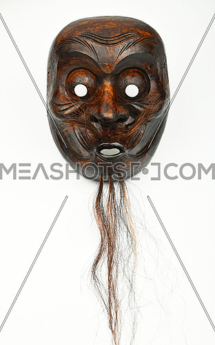 Japanese wooden carved theater mask of human face with beard and moustache isolated on white background