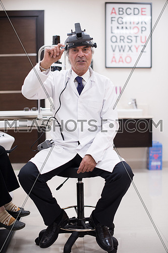 portrait of an elderly middle eastern ophthalmologist in his office in the modern clinic