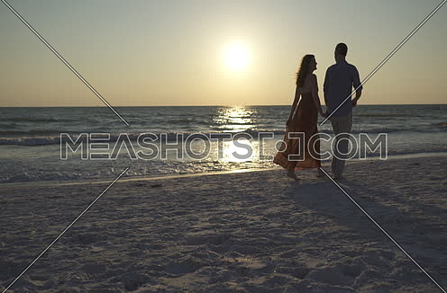 A couple holding hands and walking by the beach at sunset