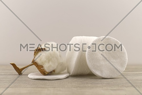 Raw cotton boll and stack of makeup remover pads. Concept of natural cotton products