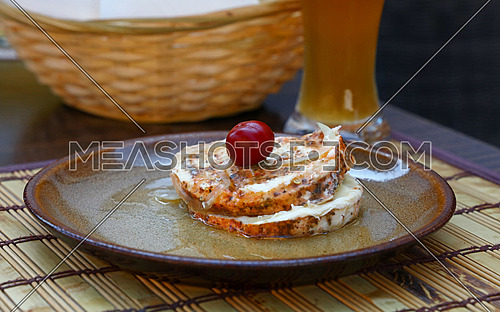 Traditional European Czech and Slovak snack starter meal for beer, nakladany hermelin, pickled marinated soft camembert cheese slices, round pepper in oil, in plate on table, close up, high angle view