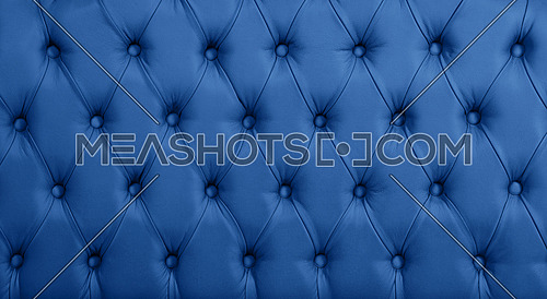 Close up background texture of dark blue capitone genuine leather, retro Chesterfield style soft tufted furniture upholstery with deep diamond pattern and buttons