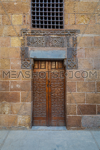 Wooden ornate door with geometrical engraved patterns on external old decorated bricks stone wall, Cairo, Egypt