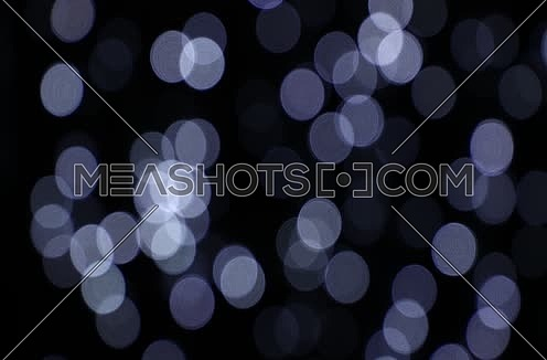 Light blue and white festive Christmas circular bokeh over dark, slow moving trembling and shaking, abstract background