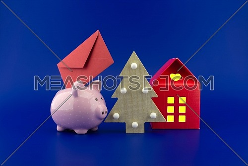 Colorful decorative Christmas still life with festive red envelope, piggy bank, Xmas tree and red building with lights in the windows over blue for a card or invitation