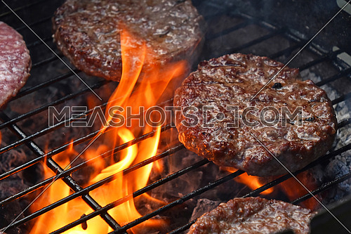 Beef or pork meat barbeque burgers for hamburger prepared grilled on bbq fire flame grill