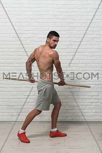 Athlete Muscular Bodybuilder Emotional Posing At The Wall With Stick