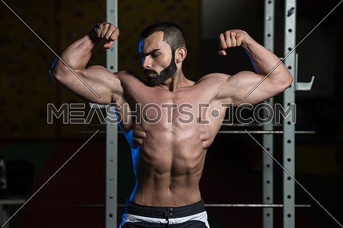 Portrait Of A Young Fit Man Performing Front Double Biceps Pose - Muscular Athletic Bodybuilder Fitness Model Posing After Exercises