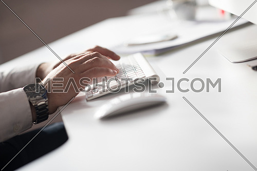 hands typing on desktop computer keyboard in modern bright office interior