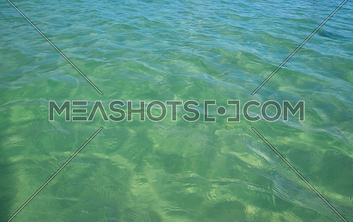 Tropical transparent clear turquoise blue sea water surface with waves and ripples, high angle view