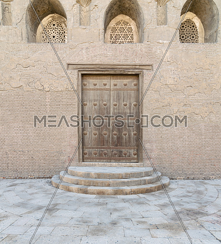 Wooden aged vaulted door, threee ornate engraved vaulted windows. three steps and stone wall, Medieval Cairo, Egypt
