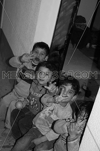 Children in a camp in Palestine holding victory sign with their fingers
