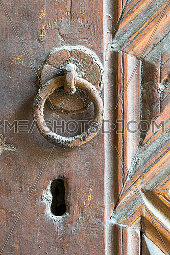 Closeup of rusted ring door knocker over an aged decorated wooden door