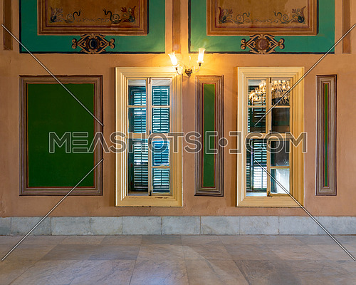 Two narrow wooden window with closed green shutters and beautiful elegant rectangular green frames on orange wall with white marble floor