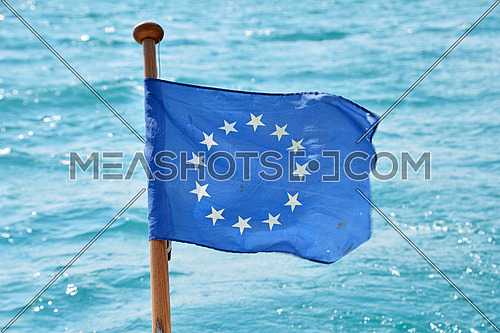 Close up flag of EU, European Union waving and blowing in the wind over blue water of sea or lake, low angle view