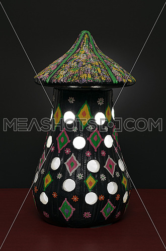 Illuminated black painted perforated pottery table lamp on black background